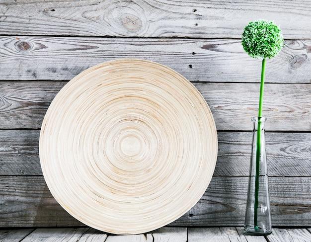 Bellissimo vaso su un bellissimo vaso su un piatto di legno con un fiore su uno sfondo di legno piatto di legno con un fiore su uno sfondo di legno