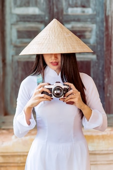 Bella ragazza vietnamita in antichi costumi nazionali in piedi per sparare di fronte a un'antica struttura