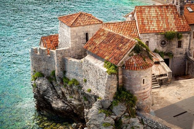 Splendida vista della città antica con tetti rossi in piedi su un'alta scogliera in riva al mare