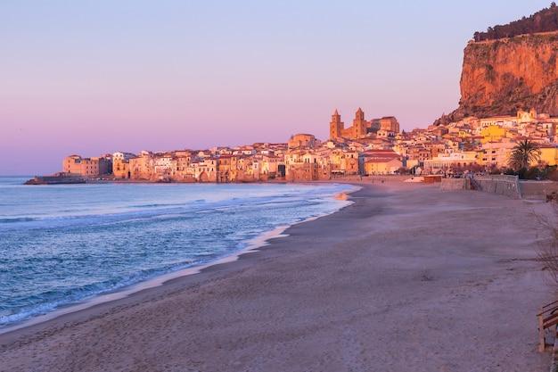 Bella vista della spiaggia vuota, della cattedrale di cefalù e della città vecchia della città costiera di cefalù al tramonto rosa, sicilia, italia