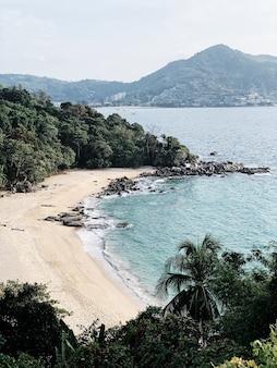 Bella vista sulla spiaggia esotica vuota con giungla, rocce e mare blu
