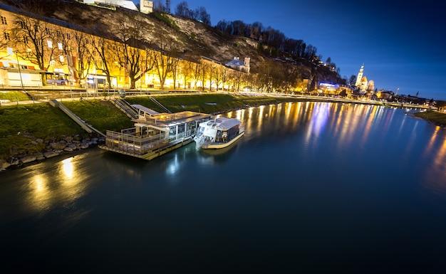 Bella vista della barca da escursione ormeggiata sul fiume di notte a salisburgo