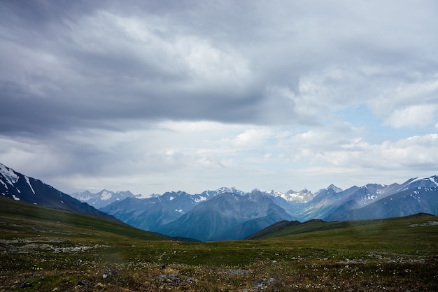 Bella vista dal passo di montagna a grandi montagne innevate sotto il cielo nuvoloso. drammatico paesaggio alpino con montagne innevate in caso di pioggia. scenario cupo con cresta di montagna gigante in una giornata nuvolosa.