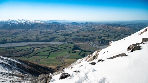 Bella vista dalla cima della montagna innevata fino alla valle verde con lo sfondo delle montagne e il cielo blu