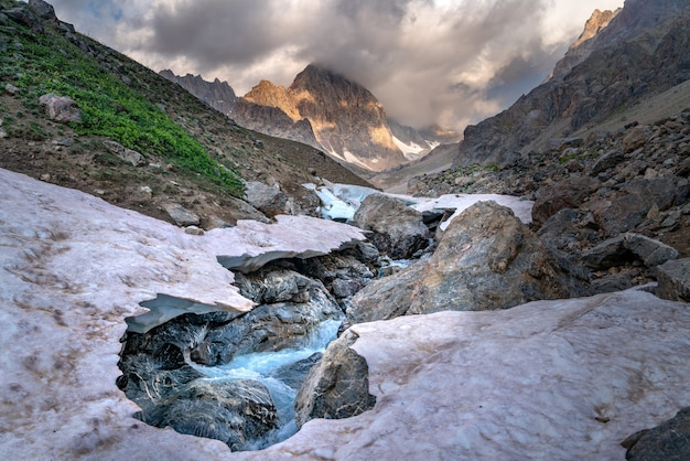 La splendida vista del ghiacciaio ghiacciato e del fiume kaznok in ordine al picco zmeya nelle montagne fann in tagikistan