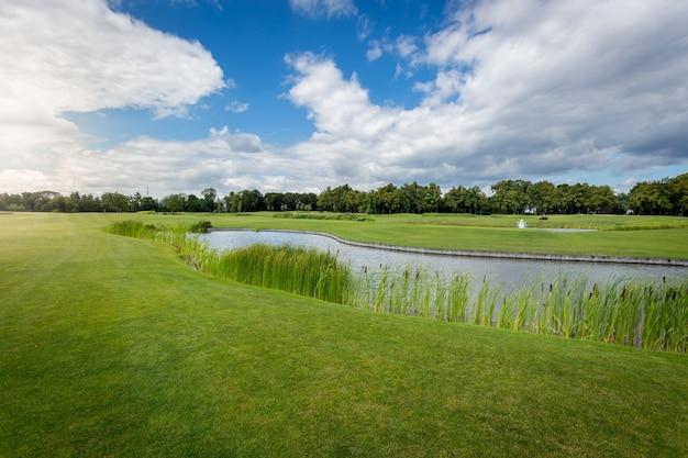Bella vista del campo da golf con ostacolo d'acqua in giornata di sole