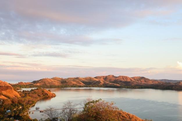 Splendida vista delle colline sul mare a labuan bajo con un drammatico cielo al tramonto