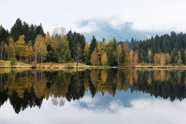 Splendida vista idilliaco paesaggio autunnale colorato con riflesso nel lago di montagna alpina in una giornata nebbiosa. austria, kitzbuhel.