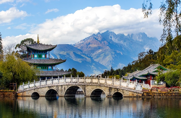 Splendida vista della jade dragon snow mountain e del ponte suocui sul black dragon pool in jade spring park, lijiang, yunnan