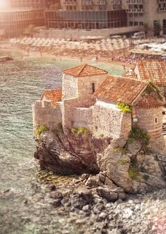 Bella vista del vecchio castello in piedi su un'alta scogliera in mare al giorno di sole