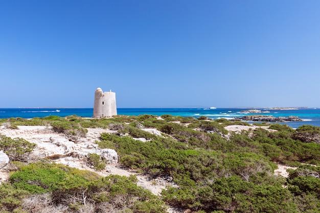 Bella vista sulla vecchia torre di osservazione e sui fari sulla costa dell'isola di ibiza.