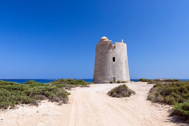 Bella vista della vecchia torre di osservazione torre de ses portes sulla costa dell'isola di ibiza.