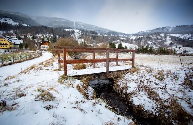 Bella vista del vecchio ponte di legno sul fiume nelle alpi austriache
