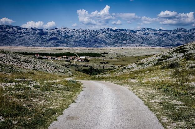 Bella vista di una strada circondata da montagne rocciose sotto un cielo nuvoloso