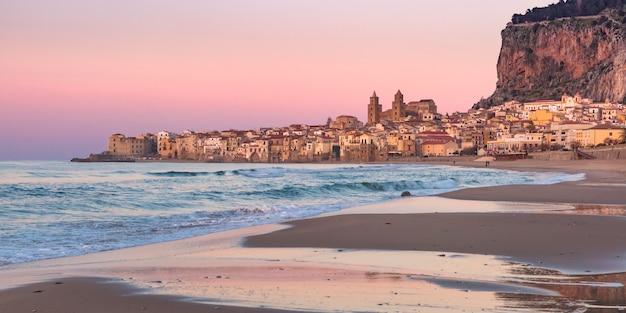 Bella vista della spiaggia di sabbia, della cattedrale di cefalù e della città vecchia della città costiera di cefalù al tramonto, sicilia, italia