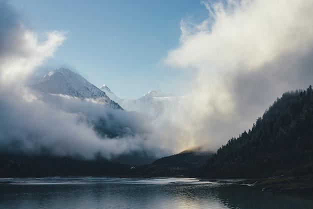 Splendida vista delle montagne innevate sopra spesse nuvole al sole. paesaggio montano panoramico con picco di neve bianca tra dense nuvole basse nel cielo blu. meraviglioso scenario alpino con pinnacolo innevato.