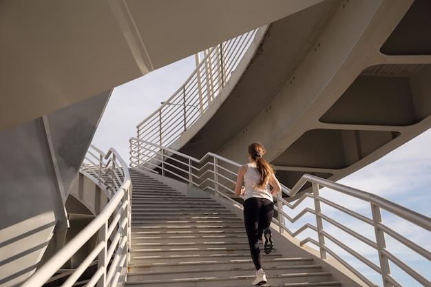 Bella vista dello sportivo che corre sulle scale al tramonto
