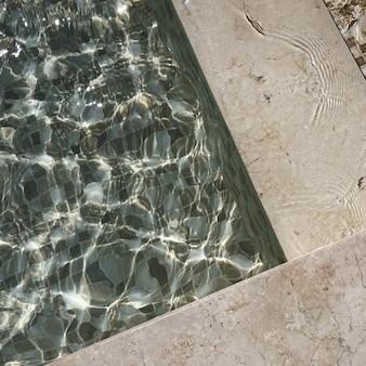 Bella vista del lato della piscina con acqua cristallina con riflessi di onde d'ombra di luce solare