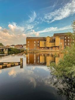 Bella vista delle tranquille acque del fiume con edifici sotto il cielo azzurro nuvoloso