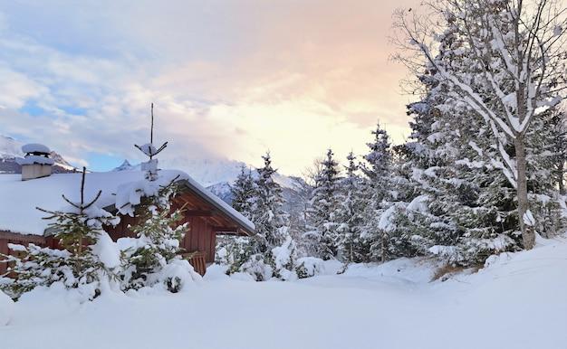 Bella vista su uno chalet alpino in legno nella neve fresca con abeti al tramonto