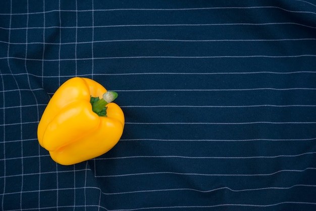Bellissimo piatto minimo di peperone giallo vivido adagiato su uno sfondo di trama dell'estratto dell'asciugamano a quadretti