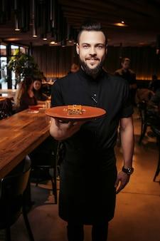 Bellissimo cameriere in abiti neri con la barba e una porzione di torta