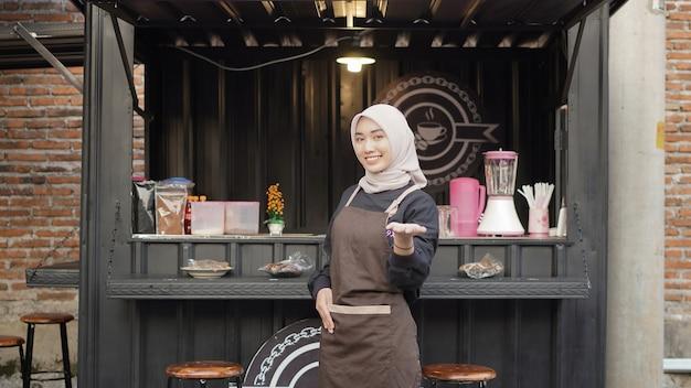 Bella cameriera che gesticola felicemente al contenitore della cabina del caffè?