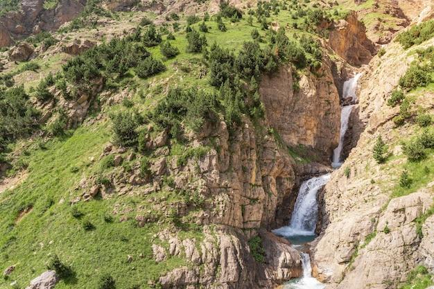 Bella cascata nel paesaggio delle montagne durante il tramonto