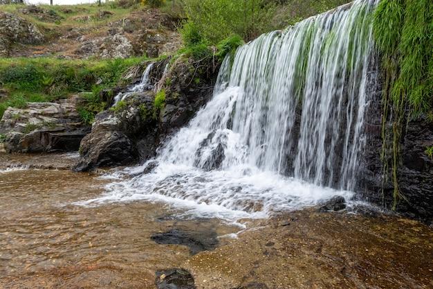 Una bella cascata sulla piscina naturale nel fiume arrago nella città di descargarmaria, spagna