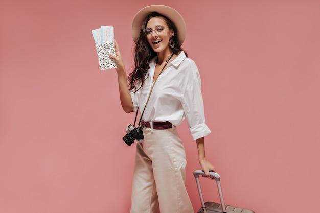 Bella donna ondulata in occhiali, cappello moderno e vestiti bianchi che sorride e posa con macchina fotografica nera, biglietti e valigia