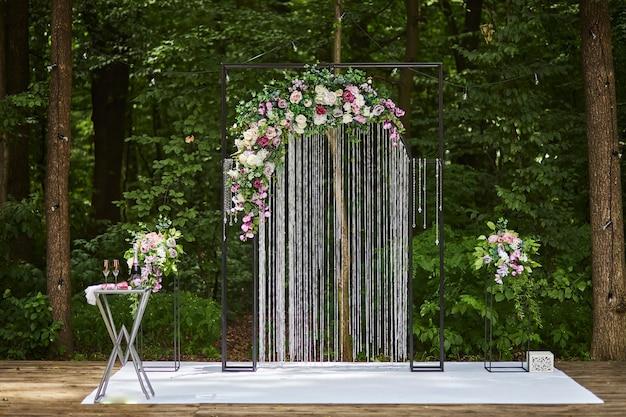 Bellissimo arco nuziale per cerimonia in stile rustico situato nella foresta