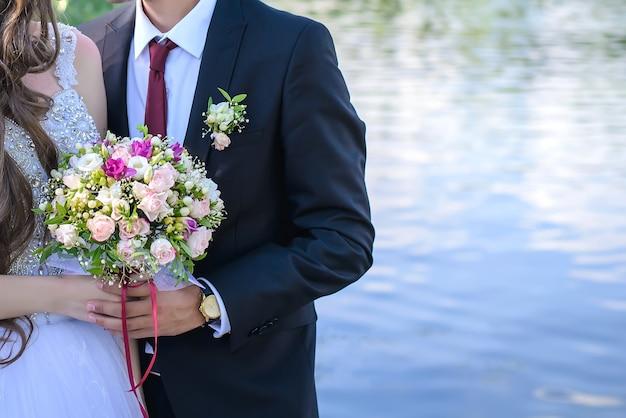 Bellissimo bouquet da sposa di delicate rose rosa nelle mani della sposa e dello sposo da vicino, copia dello spazio