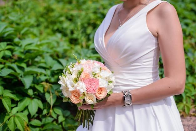 Bellissimo bouquet da sposa di delicate rose rosa e bianche nelle mani della sposa in un primo piano del vestito bianco