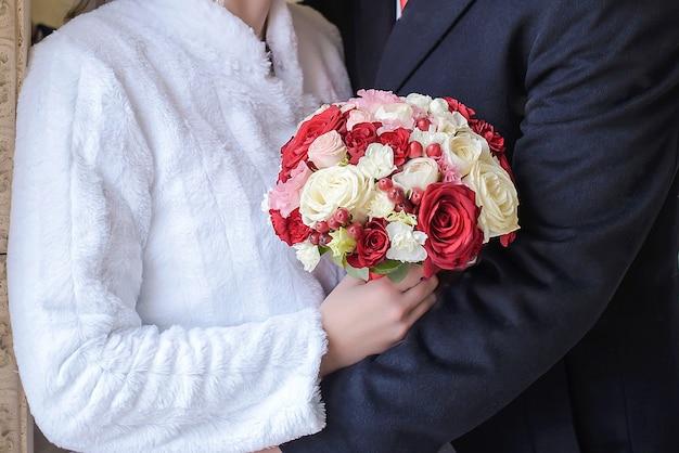 Bellissimo bouquet da sposa nelle mani del primo piano dello sposo e della sposa