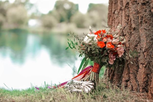 Bellissimo bouquet da sposa vicino al tronco di un grande albero