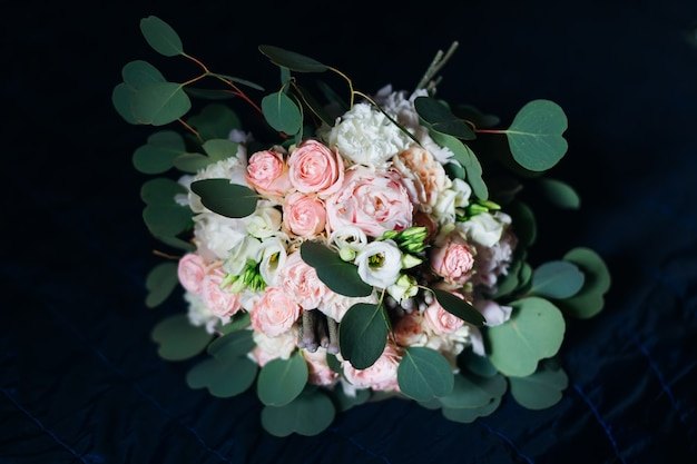 Bellissimo bouquet da sposa di rose su una coperta scura.