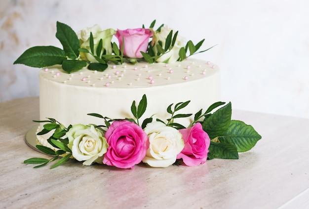 Bella torta nunziale con i fiori sulla tavola di marmo e sul fondo bianco