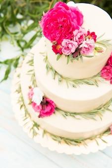 Bella torta nuziale con fiori, all'aperto. tre livelli