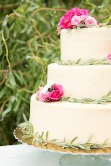 Bella torta nuziale con fiori all'aperto