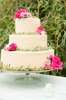 Bella torta nuziale con fiori, all'aperto