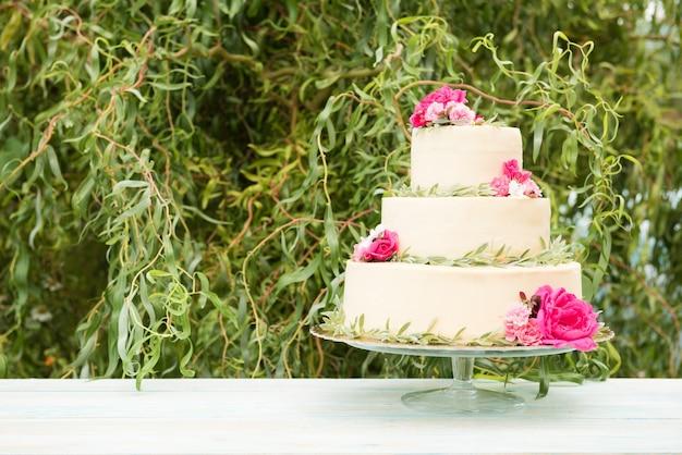 Bella torta nuziale con fiori sul tavolo all'aperto