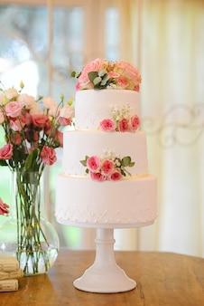 Bella torta nuziale con tre livelli e rose fresche