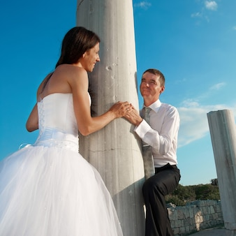 Bella sposa e sposo delle coppie di nozze vicino alla colonna della grecia nella città antica