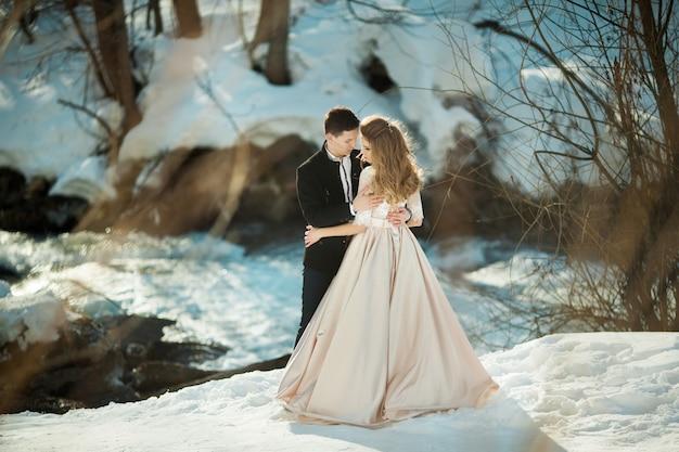 Bella coppia di sposi in riva al fiume