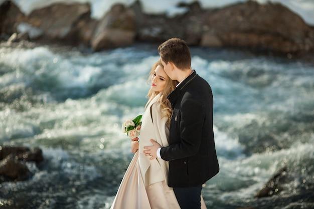 Bella coppia di sposi in riva al mare