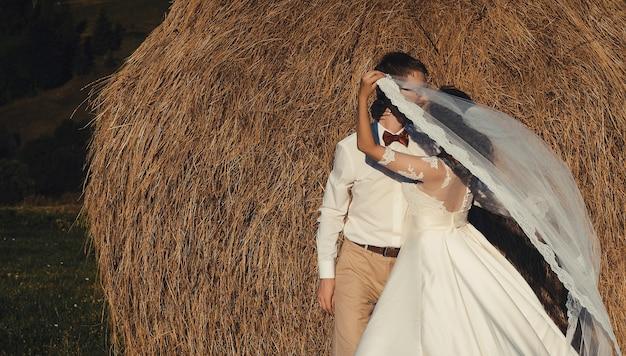 Bellissimo matrimonio in montagna, una giovane coppia felice vicino al fienile.