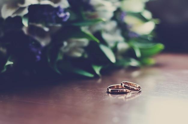 Bellissime fedi nuziali giacciono su una superficie di legno sullo sfondo di un mazzo di fiori