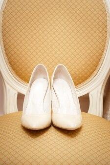 Le bellissime scarpe da sposa sulla sedia