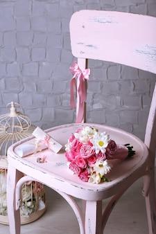 Bellissimo matrimonio ancora in vita con bouquet su sedia in legno