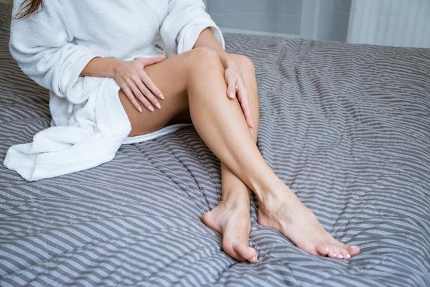 Bei piedi ben curati sul letto. concetto di cura della pelle del piede a casa